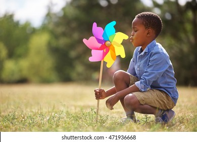 African kid playing with pinwheel at the park