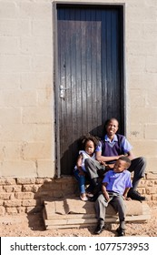 African kids sitting infront of their house in the township.