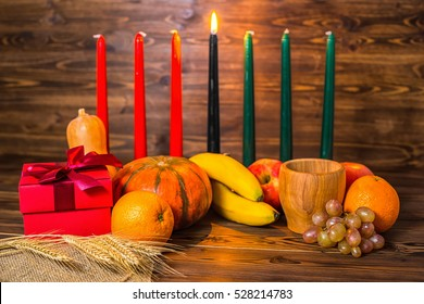 african Kwanzaa festive concept with decorative candles red, black and green, gift box, pumpkins, ears of wheat, grapes, orange, banana, bowl and fruits on wood background