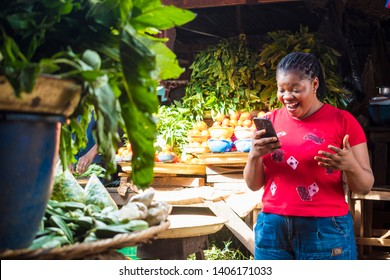 african lady in a local market surprised and excited by something she's viewing on a phone