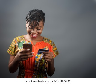 African lady making a mobile payment using a credit card