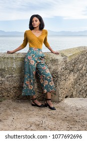 African lady standing against a rock wall with the mountains in the background.