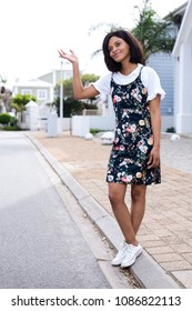 African lady waving while standing outside and wearing a floral dress.