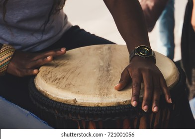 An African or Latin brown djembe conga drum being played against. Hands of the Negro women from Nigeria beating the drum