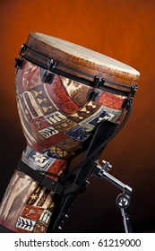 An African or Latin djembe drum isolated against a spotlight gold background.