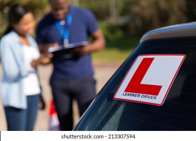 african learner driver and instructor behind a car