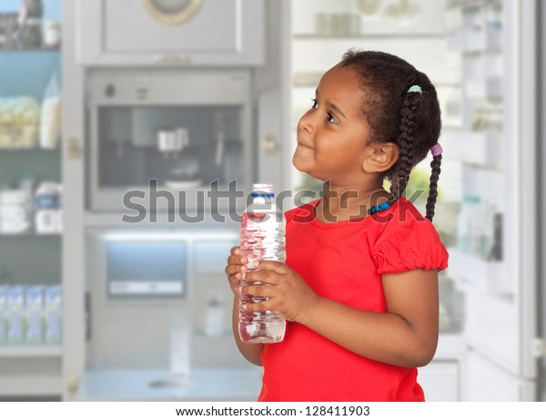 African little girl with water bottle in the kitchen