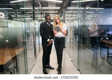 African male and caucasian female office workers with tablet pc standing at empty office corridor and discussing new project.