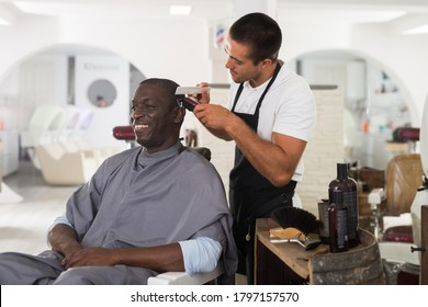African male client getting haircut at barber shop from professional hairstylist using clipper