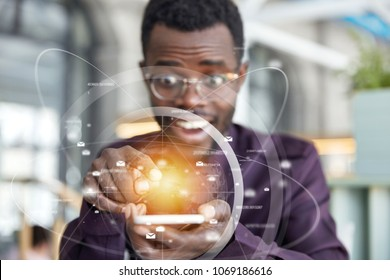 African male enterpreneur holds modern cell phone with futuristic mobile application in hands, sends messages, has overjoyed expression. Double exposure and visual effects. Focus on electronic device