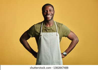 African male farmer with muscular hands and sportive body, dressed in apron smiling at camera with toothy smile over yellow background. People Profession, Emotions