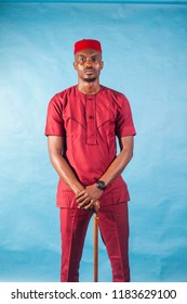 African male fashion model dressed in maroon traditional attire.