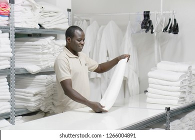 An African male hotel worker folds a clean white towel. Hotel staff workers. Hotel linen cleaning services.