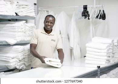 African male hotel worker folds a clean white towel. Hotel staff workers. Hotel linen cleaning services.
