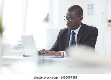 African male leader concentrating at his work at office he sitting at the table and typing on computer