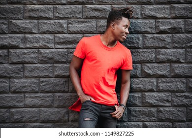 African male model standing in empty red t-shirt against brick wall