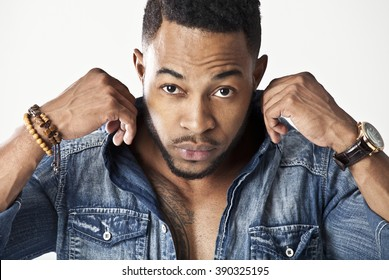 African male model wearing a jean shirt looking very serious holding his collar