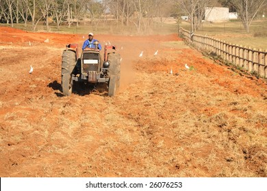 African male on a tractor tilling soil