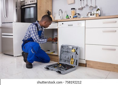 African Male Plumber Fixing Sink Pipe In Kitchen