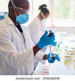 Afrikanischer Techniker, der eine Gesichtsmaske trägt und bei der Arbeit an einem Labortisch mit einem Kollegen Proben analysiert