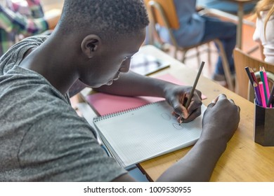 African male teenager making lesson in the classroom and worried about the test.