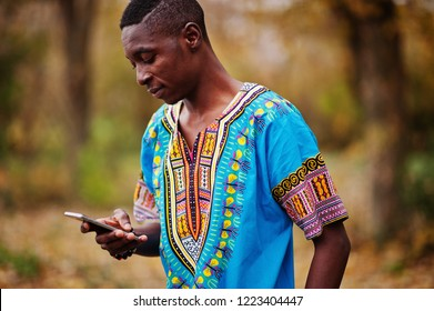 African man in africa traditional shirt on autumn park.
