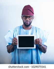 African man in an Agbada attire holding a tablet device
