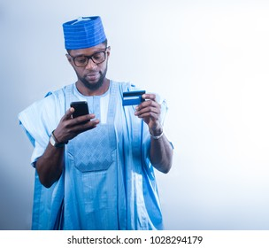 African man in Agbada making a payment with his mobile phone