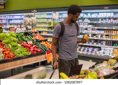 African man with beard standing in supermarket, choosing fruits. Vegetable and milk showcases on background