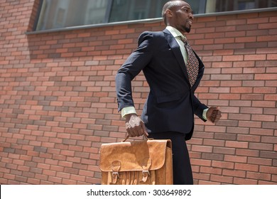 The african man as black businessman with a briefcase running in a city street on a background of red brick wall