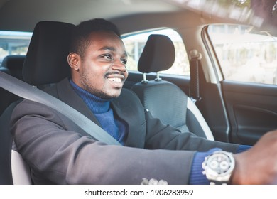 African man in a black suit sitting behind the wheel with smile and happy