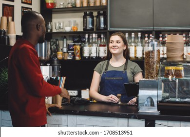 African man buys a cup of coffee at a bar counter at a barista in a cafe.