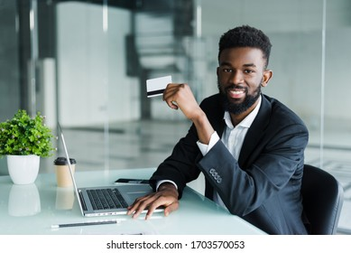 African man in casual outfit talking on phone and reading credit card number while sitting at office