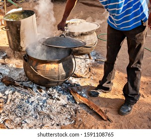 african man cooking in few huge pots in the backyard in the village in a rural area