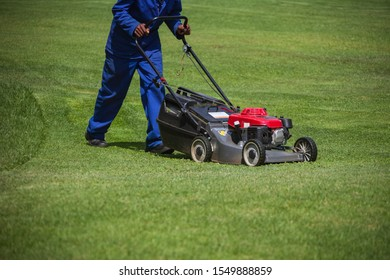 African man cutting grass with a lawnmower,