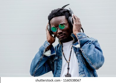 African man with dreadlocks in denim jacket listening to music in headphones standing on white wall background closeup