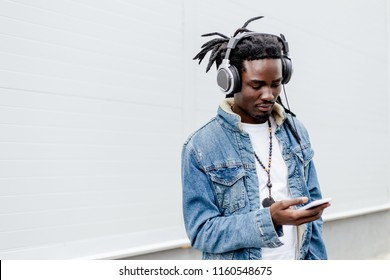 African man with dreadlocks in denim jacket listening to music in headphones holding the phone