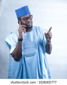African man dressed in an Agbada on a phone call.