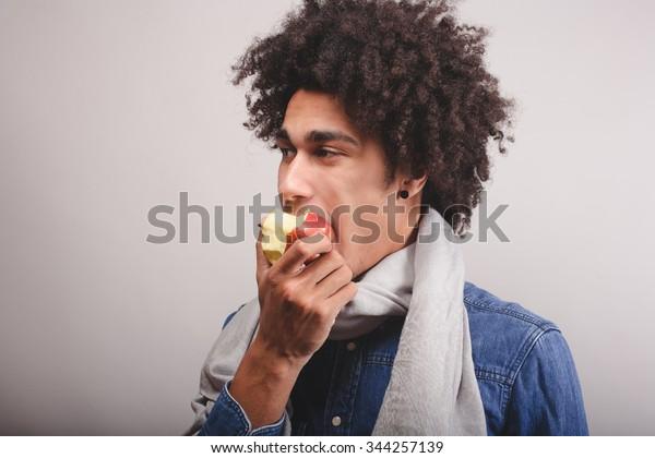 African man eating an apple