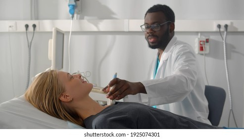 African man endocrinologist making ultrasonography to female patient in ultrasound office. Afro-american doctor making ultrasound diagnostics of thyroid gland
