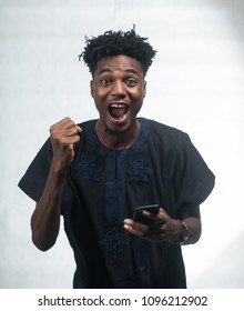 African man excited at his mobile phone