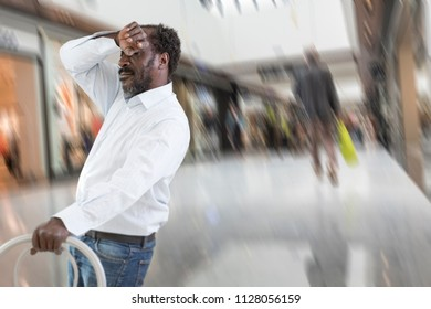 African Man Feeling A Big Pain Collapsing holdin a chair -man who feels bad, unwell hand on his forehead