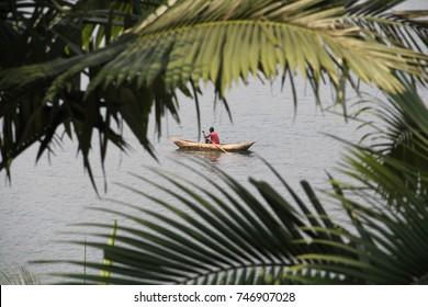 An African man fishing from his dugout canoe on Lake Kivu, Rwanda, viewed through palm fronds