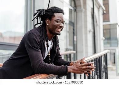 African man with glasses leaning on the railing stands in the city block smiling broadly