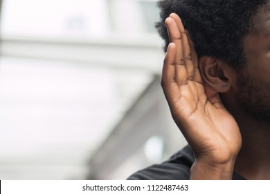 african man hearing or listening; portrait man listening to hearsay, rumor, gossip, good or bad news; communication, information, rumor concept; african man or black man young adult model