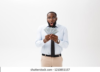 African man holding bank notes happy and surprised cheering expressing wow gesture