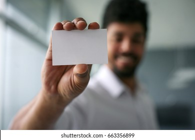 African man holding a blank business card. Focus on blank card. Space for copy.