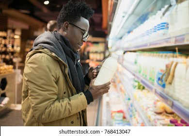 African man holding and choice milk or yogurt bottle in supermarket showcase, healthy food concept