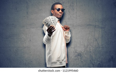 African man holding dollar bank notes proud, excited and arrogant, pointing with victory face
