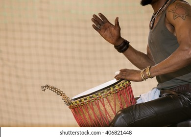 African man playing drum with hands, one hand raised, palm view